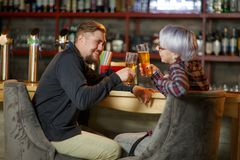 A pair sit in a bar and Cheers with glasses of beer. Indoors. stock photos