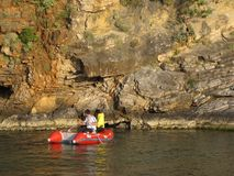 A pair of young people in sports clothes row around the rocks lit by sunlight on a rubber inflatable boat of red color. Peering cl stock photo