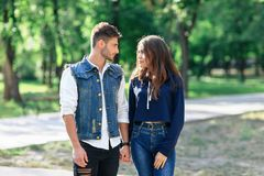 Pair of young people standing in park looking each other Royalty Free Stock Images