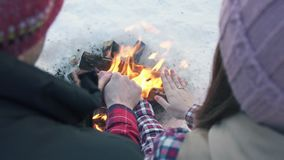 A pair of young people with wedding rings in winter clothes in the woods, warm their hands by the fire, winter holidays. A pair of young people with wedding stock footage