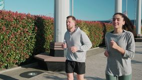 Young man and woman are jogging together in sunny morning outdoors stock footage
