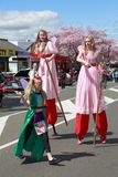Two female stilt walkers in long pink dresses royalty free stock photography