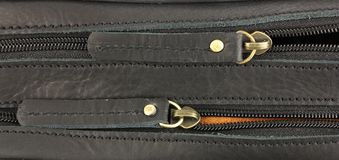 Pair of zippers on the black leather bag, one behind stock photography