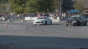 Paired car drift show. NOVOSIBIRSK, RUSSIA - JUNE 03, 2016: Pair of cars drifting together during competitions stock video footage