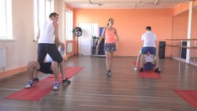 Paired classes in a modern fitness center with caucasian guys, group sports in the gym to strengthen muscles and lose. Weight, healthy lifestyle stock video