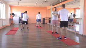 Paired classes in a modern fitness center with caucasian guys, group sports in the gym to strengthen muscles and lose. Weight, healthy lifestyle stock video footage