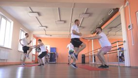 Paired classes in a modern fitness center with caucasian guys, group sports in the gym to strengthen muscles and lose. Weight, healthy lifestyle stock footage
