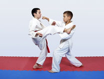 Paired exercises karate athletes with white and red sash. Paired exercises karate sportsmen with white and red sash Stock Photography