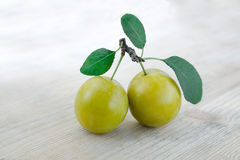 Paired fruits. Two plums on one stalk with green leaves. Wooden background. Paired fruits. Two yellow plums on one stalk with green leaves. Wooden background Stock Photography