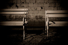 Paired on the street. Two vintage benches  on the street Stock Images