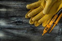 Paires électriques d'appareil de contrôle de gants de sécurité sur le conseil en bois photographie stock