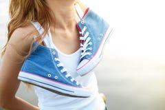 Paires attachées d'espadrilles accrochant sur une fille Image stock