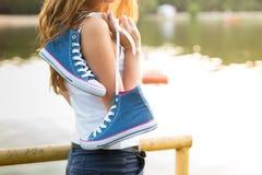 Paires attachées d'espadrilles accrochant sur une fille Image libre de droits