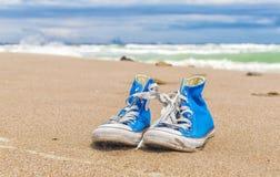 Paires bleues d'espadrilles usées sur le sable de plage Photos stock