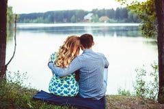 Paires d'amants reposant sur le rivage le lac tourné loin Photo libre de droits