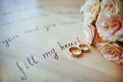 Paires d'anneaux de mariage dans des couleurs chaudes, avec les roses jaunes d'un bouquet Image stock
