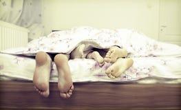 Paires d'arbre de jambes dans le lit Photos libres de droits