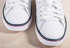 Paires d'entraîneurs lacés à la mode blancs sur la surface en bois Image libre de droits