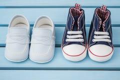 Paires d'espadrilles bleu-foncé et blanches de bébé et de chaussures de bébé bleu Image libre de droits