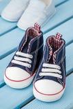 Paires d'espadrilles bleu-foncé et blanches de bébé et de chaussures de bébé bleu Images libres de droits