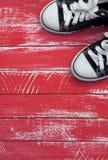 Paires d'espadrilles bleues dans un coin d'un fond rouge minable, VE Photographie stock libre de droits