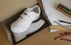 Paires d'espadrilles dans la boîte en carton de chaussure sur la table d'étudiant Photos stock