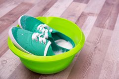 Paires d'espadrilles de turquoise en bassin en plastique avec des lessives Photographie stock libre de droits