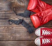 Paires d'espadrilles rouges de textile et de gants de boxe en cuir rouges Photos libres de droits