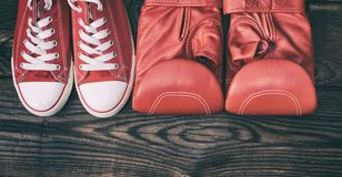 Paires d'espadrilles rouges et de gants de boxe en cuir rouges Photographie stock libre de droits