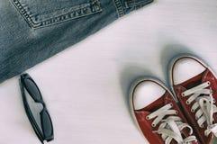 Paires d'espadrilles rouges, rétros jeans de fragment, lunettes de soleil noires dessus Photographie stock libre de droits