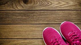 Paires d'espadrilles rouges sur le fond en bois Sports et Ba de forme physique Photographie stock libre de droits