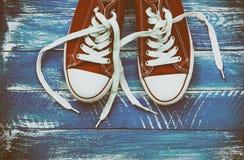 Paires d'espadrilles rouges sur une surface en bois minable bleue Photographie stock