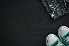 Paires d'espadrilles, un fragment des jeans et écouteurs sur un noir Photographie stock