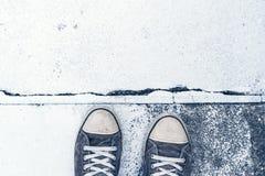 Paires d'espadrilles usées sur le plancher en béton Photographie stock libre de droits