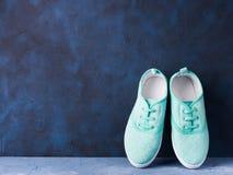 Paires d'espadrilles vertes de toile de femme sur le fond bleu Photographie stock