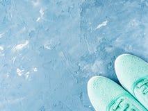 Paires d'espadrilles vertes de toile de femme sur le fond bleu Photo stock