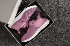 Paires d'espadrilles violettes dans la boîte en carton de chaussure sur le fond gris Image stock