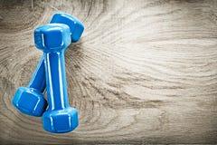 Paires d'haltères bleues sur le concept en bois de forme physique de l'espace de copie de conseil Image stock