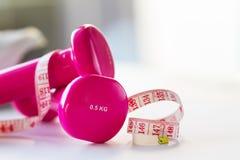 Paires d'haltères roses de forme physique avec le ruban de centimètre sur lumineux Images libres de droits