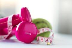 Paires d'haltères roses de forme physique avec le ruban de centimètre sur lumineux Image stock