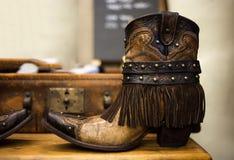 Paires de bottes en cuir brunes faites main de cow-girl avec le suitca de vintage photo stock