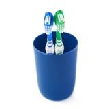 Paires de brosses à dents dans la tasse en plastique bleue d'isolement au-dessus du fond blanc Images libres de droits