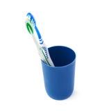 Paires de brosses à dents dans la tasse en plastique bleue d'isolement au-dessus du fond blanc Photographie stock
