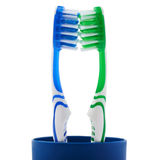 Paires de brosses à dents dans la tasse en plastique bleue d'isolement au-dessus du fond blanc Photo stock
