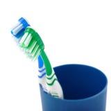Paires de brosses à dents dans la tasse en plastique bleue d'isolement au-dessus du fond blanc Photographie stock libre de droits