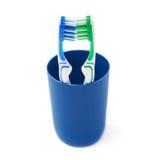 Paires de brosses à dents dans la tasse en plastique bleue d'isolement au-dessus du fond blanc Photo libre de droits