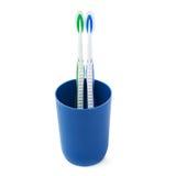 Paires de brosses à dents dans la tasse en plastique bleue d'isolement au-dessus du fond blanc Photos stock