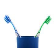 Paires de brosses à dents dans la tasse en plastique bleue d'isolement au-dessus du fond blanc Image libre de droits