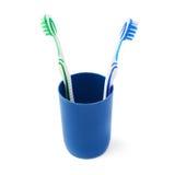 Paires de brosses à dents dans la tasse en plastique bleue d'isolement au-dessus du fond blanc Photos libres de droits