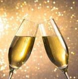 Paires de cannelures de champagne avec les bulles d'or sur le fond clair de bokeh Image stock